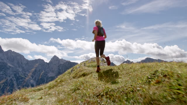 slo mo female runner running on the edge of a mountain ridge in sunshine - top garment stock videos and b-roll footage