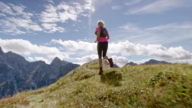 SLO MO Female runner running on the edge of a mountain ridge in sunshine