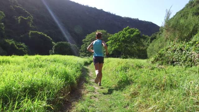 vidéos et rushes de coureur de femme traversant une vallée d'herbe - joggeuse