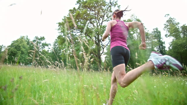 SLO MO TS Female runner running through high grass
