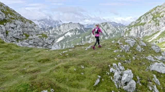 aerial weibliche läufer läuft auf dem berggipfel im sonnenschein - oberteil stock-videos und b-roll-filmmaterial