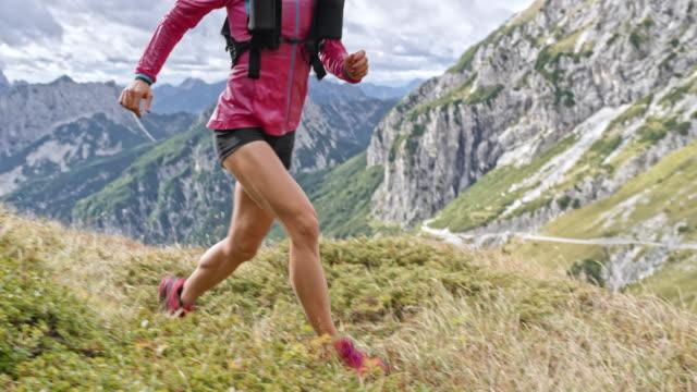 SLO MO DS vrouwelijke loper loopt naar de top van de berg in de zon