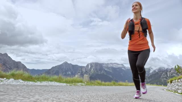 slo mo weibliche läufer laufen auf einer bergstraße an einem bewölkten tag - rotes haar stock-videos und b-roll-filmmaterial