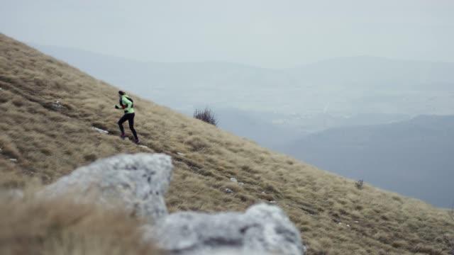 曇りの天候で山の斜面を実行している女性ランナー - full length点の映像素材/bロール