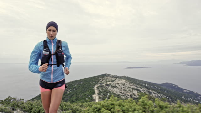 Female runner running up a rocky mountain overlooking the Adriatic sea on a cloudy day