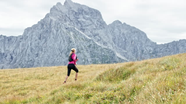 ds female runner running up the meadow high in the mountains on a sunny day - pedal pushers stock videos & royalty-free footage