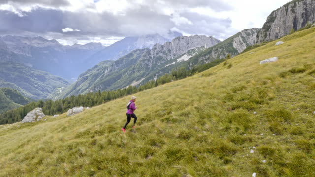 vídeos de stock, filmes e b-roll de aerial runner feminino correr até os prados de montanha - menos zoom