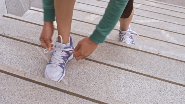ld female runner stopping on stairs to tie shoelace - shoelace stock videos and b-roll footage