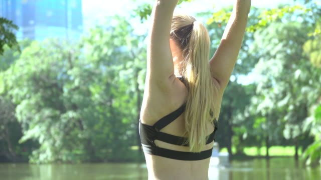 female runner stretching arms in park - self improvement stock videos & royalty-free footage