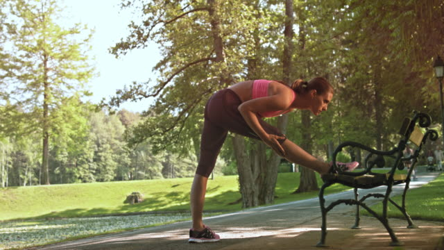 DS Female runner stretching her legs on a park bench