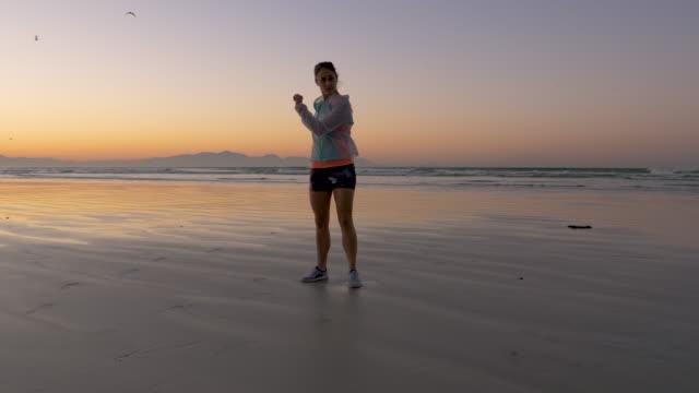 vídeos y material grabado en eventos de stock de female runner stretching on a beach at dawn - corredora de footing