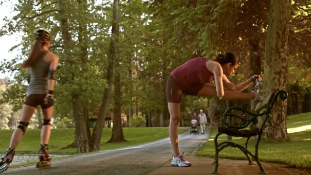 vídeos y material grabado en eventos de stock de ds mujer corredor de estiramiento en banco del parque - corredora de footing