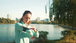 Female runner using her smartphone while exercising.