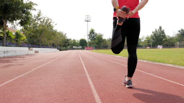 female runner warm up before running at sport stadium - warming up stock videos & royalty-free footage