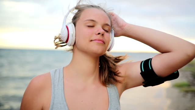 female runner with headphones and arm sport band listening to music in pause - arm band stock videos & royalty-free footage