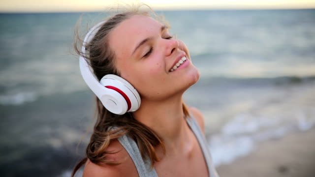 female runner with headphones and arm sport band listening to music in pause - ascoltare video stock e b–roll