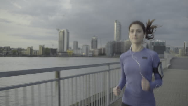 vídeos de stock, filmes e b-roll de female runner with headphones jogging by river at sunset - rio tâmisa