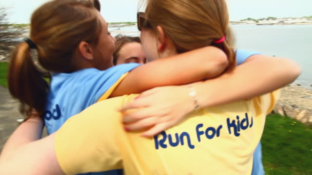 cu female runners celebrating after charity run / salem, massachusetts, usa - charity benefit stock videos & royalty-free footage