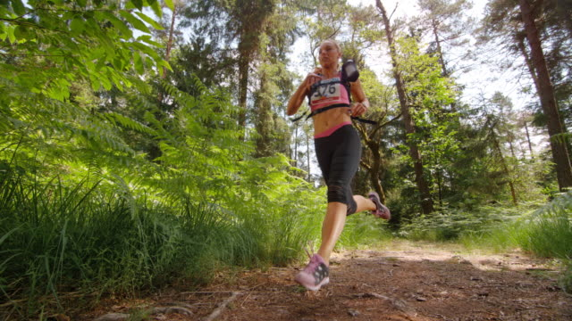 SLO MO CS Female running a marathon across a forest clearing
