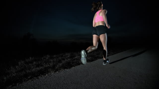 slo mo pan female running at night - running shorts stock videos and b-roll footage