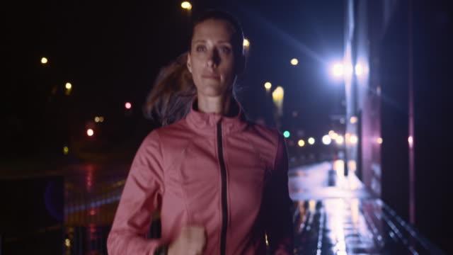 SLO MO vrouwelijke lopen in de stad bij nacht