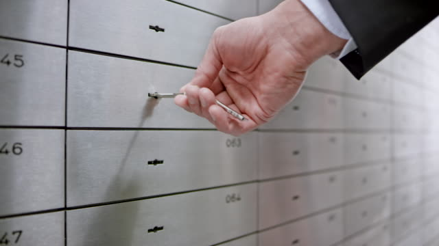 female safe deposit box clerk unlocking the safe box for a customer granting him access to his valuables - safety stock videos & royalty-free footage