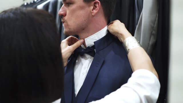 female sales assistant helping customer with bowtie - tuxedo stock videos and b-roll footage