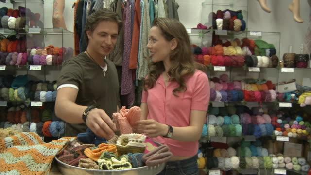 MS, DS, Female sales clerk assisting man in knitting store, Berlin, Germany