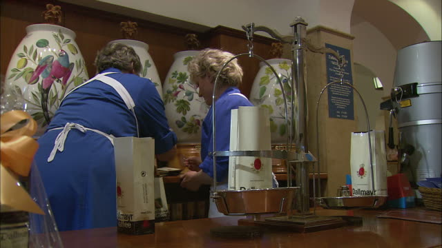 ms female sales clerk weighting coffee at dallmayr, luxury delicatessen, munich, bavaria, germany - porcelain stock videos & royalty-free footage