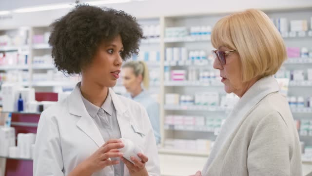 female salesperson at the drugstore advising a senior woman about a mineral supplement - pharmacy stock videos & royalty-free footage