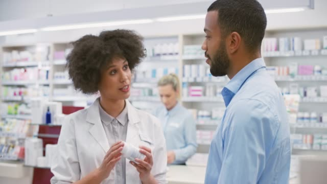 female salesperson at the drugstore advising a young man about a vitamin supplement - vitamin stock videos & royalty-free footage