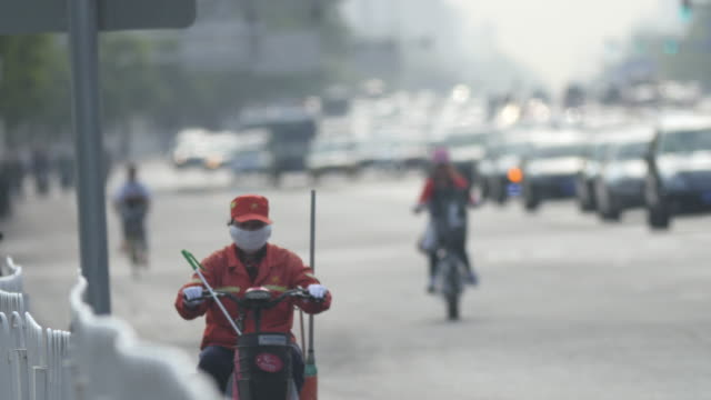 female sanitation worker wearing mask in traffic in beijing, china - dustman stock videos & royalty-free footage
