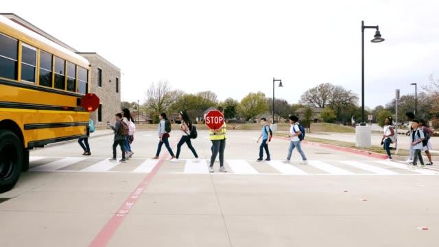 vidéos et rushes de la garde de passage d'école femelle aide les écoliers à traverser la rue - petits garçons