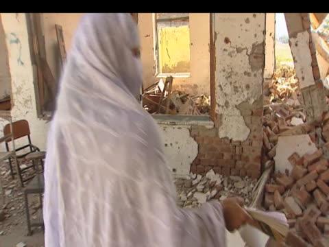 female school teacher walks around remains of destroyed school following taliban bomb attacks pakistan; 15 october 2009 - lärarinna bildbanksvideor och videomaterial från bakom kulisserna