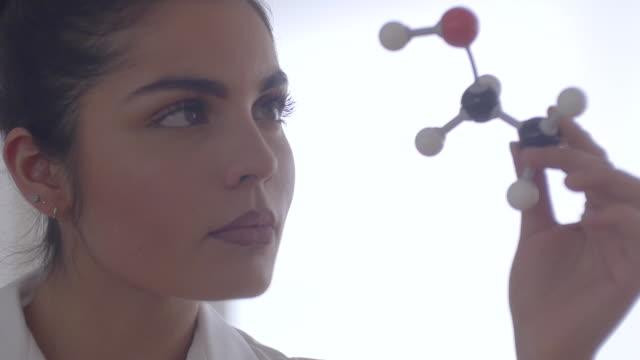 Female scientisit examining molecular model