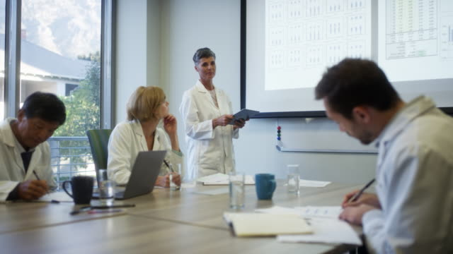 female scientist discussing with colleagues - tavolo da conferenza video stock e b–roll