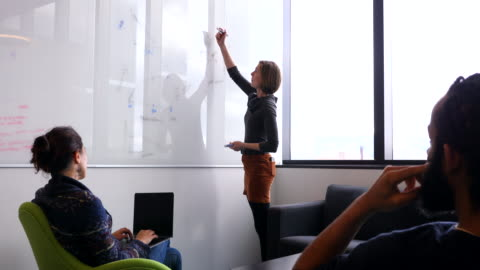 ms female scientist explaining data on whiteboard to colleagues in conference room in research lab - research stock-videos und b-roll-filmmaterial