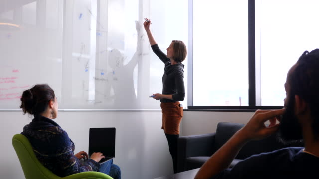 ms female scientist explaining data on whiteboard to colleagues in conference room in research lab - data stock videos & royalty-free footage
