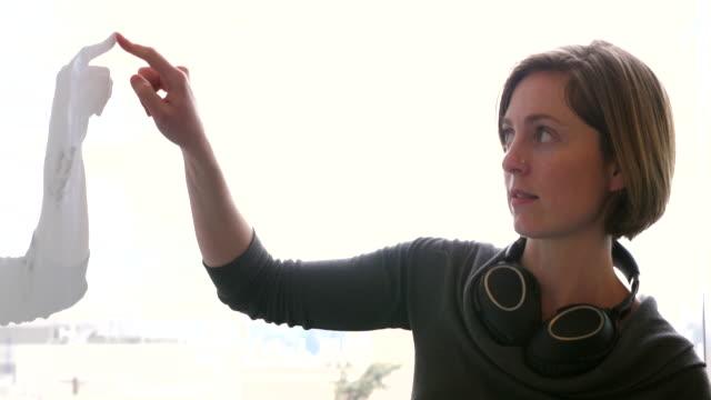 ms female scientist explaining data on whiteboard to colleagues in conference room in research lab - förklara bildbanksvideor och videomaterial från bakom kulisserna