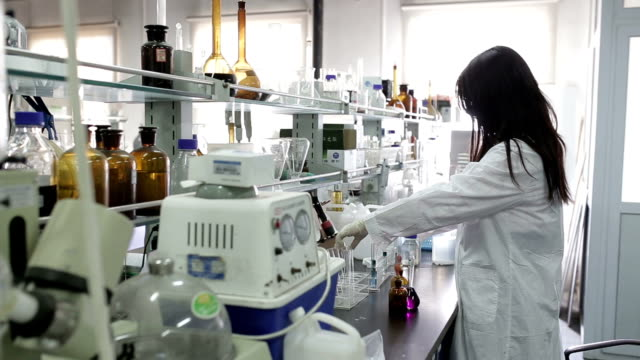 a female scientist in laboratory - laboratory stock-videos und b-roll-filmmaterial