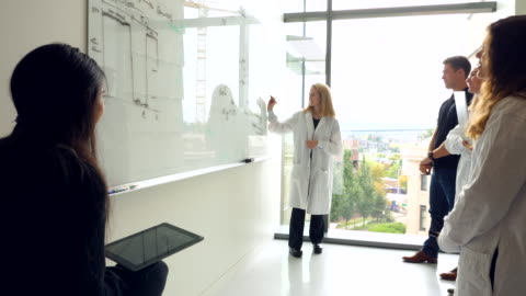 ms female scientist leading discussion of experiment results with colleagues at white board in laboratory - wissenschaft stock-videos und b-roll-filmmaterial