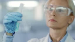 Female Scientist Looking at Vaporizing Chemical Substance in Test Tube