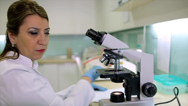 Female Scientist looking through a microscope in a laboratory,microbiology