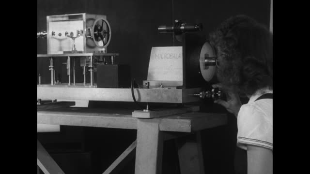female scientist peers through viewfinder into rectangular contraption / shiny metal wheel / the bespectacled lady looking through viewfinder - scienziata video stock e b–roll
