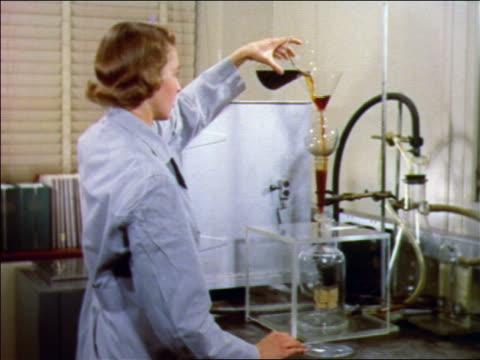 1957 female scientist pouring brown liquid into glass container in laboratory / bell labs - scienziata video stock e b–roll