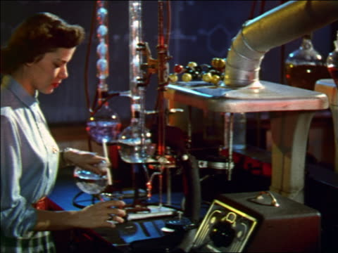 1956 female scientist pouring clear liquid from round glass container to beaker in laboratory - scientific experiment stock videos & royalty-free footage