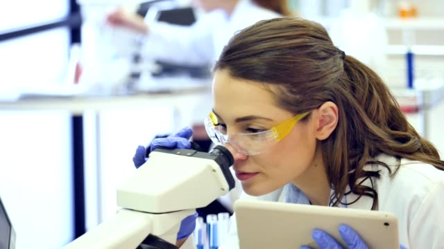 female scientist uses digital tablet and microscope in research lab - centro di ricerca video stock e b–roll