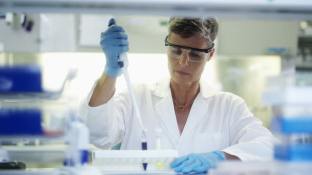 female scientist using pipette for pouring sample - pipette stock videos & royalty-free footage