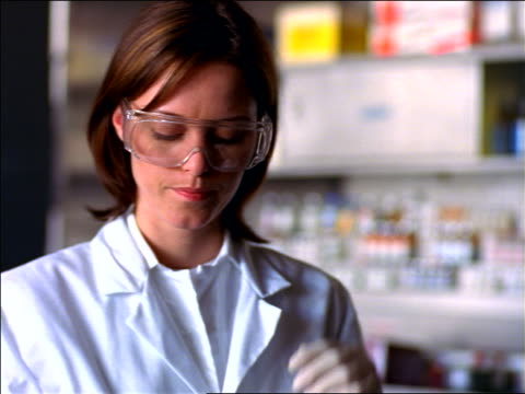 female scientist with goggles putting on rubber gloves in lab - medical glove stock videos & royalty-free footage