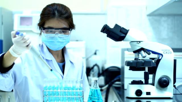 wissenschaftlerin mit weißem schutzanzug mit pipette fill chemical substance in teströhren und blick ins mikroskop während wissenschaftlicher experimente im labor - 4k - phiole stock-videos und b-roll-filmmaterial